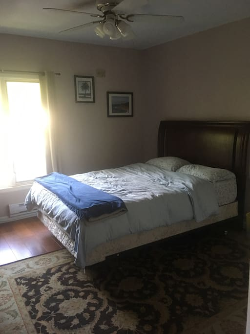 Queen size bed with desk and full bathroom.