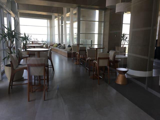Lounge onde é servido o café da manhã com uma linda vista da orla.