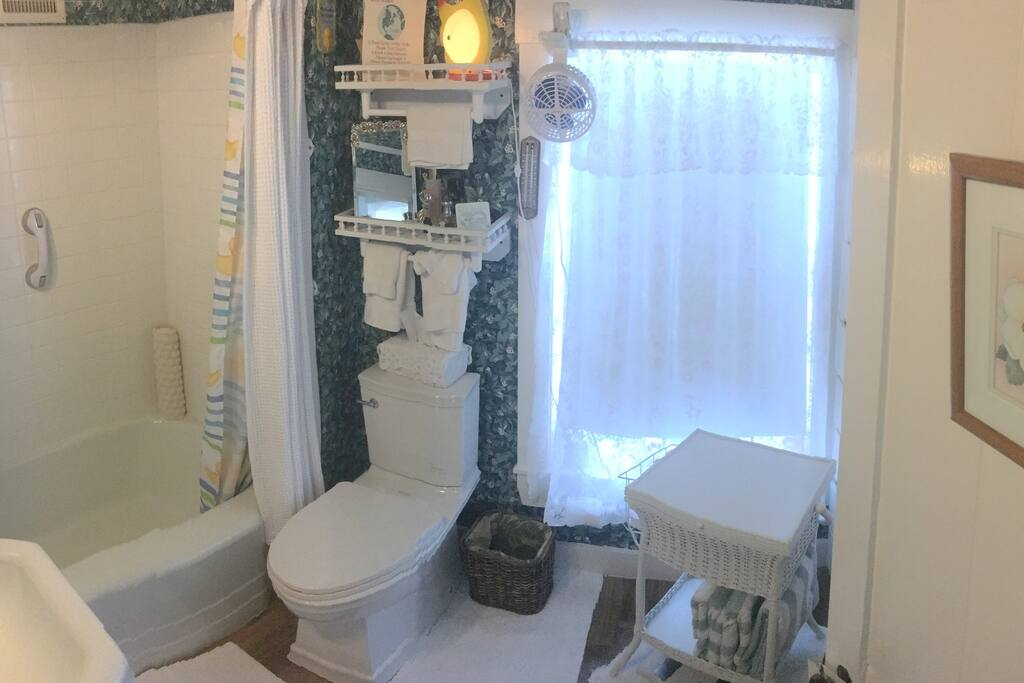Very clean guest bathroom with bathtub and shower.