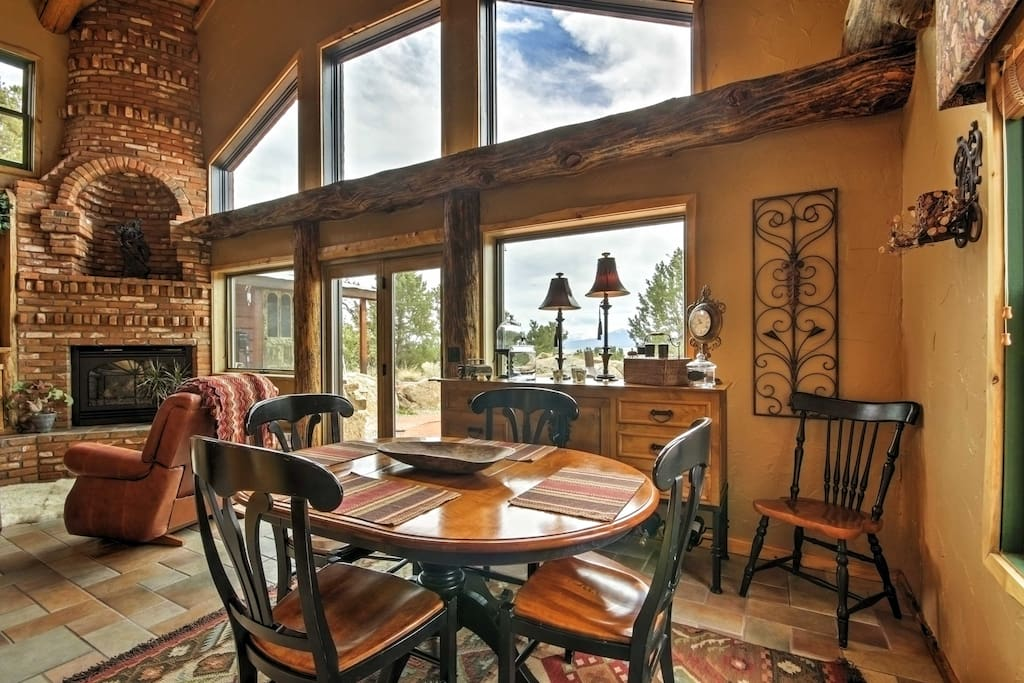 This gorgeous custom built log home features tall ceilings, floor to ceiling windows, and natural wooden beams.