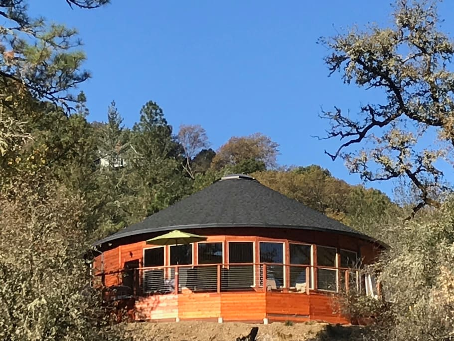 Deck-wrapped round house nestled in the hillside