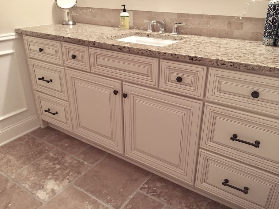 Bathroom with marble floors and granite countertop.