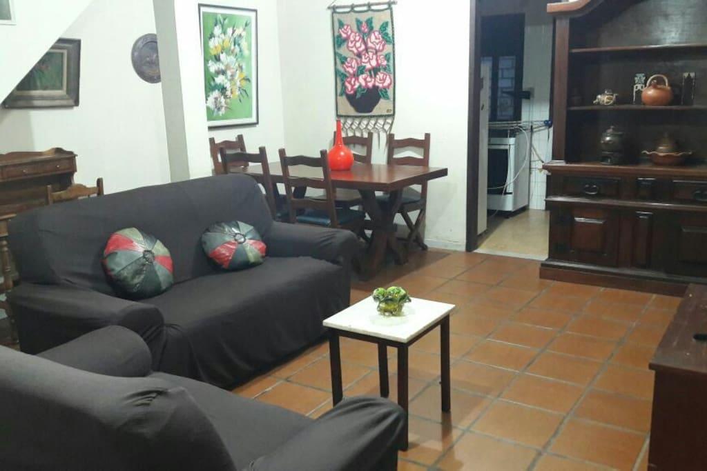 Ampla sala de estar com 2 sofás, televisão, mesa de jantar, ventilador de teto e escada de acesso ao segundo andar.