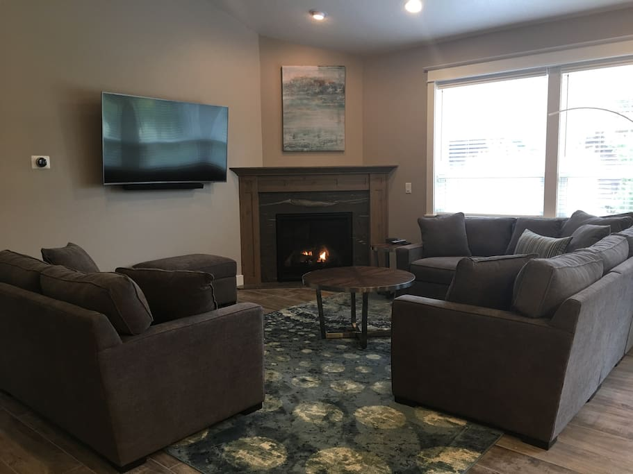 """Cozy living space with sectional, love seat, fireplace, and 65"""" TV with Blue Ray player"""