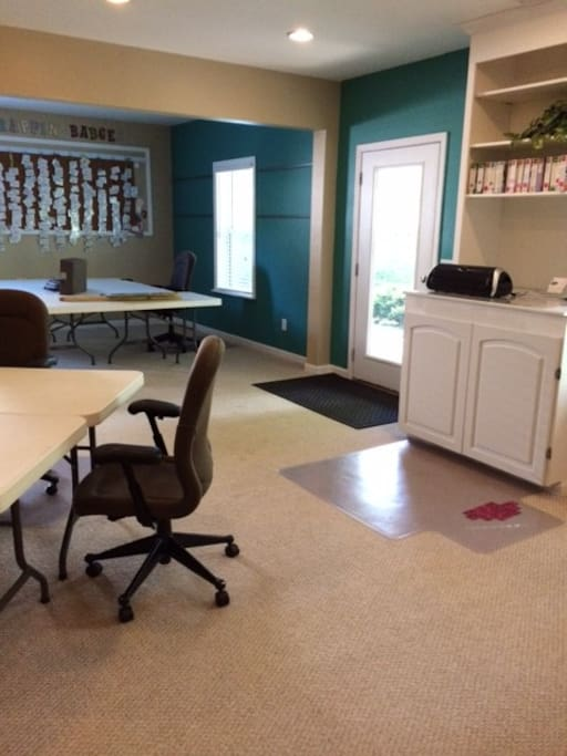The cropping room downstairs features 3 pods of tables, work stations containing scrapbooking tools and supplies.