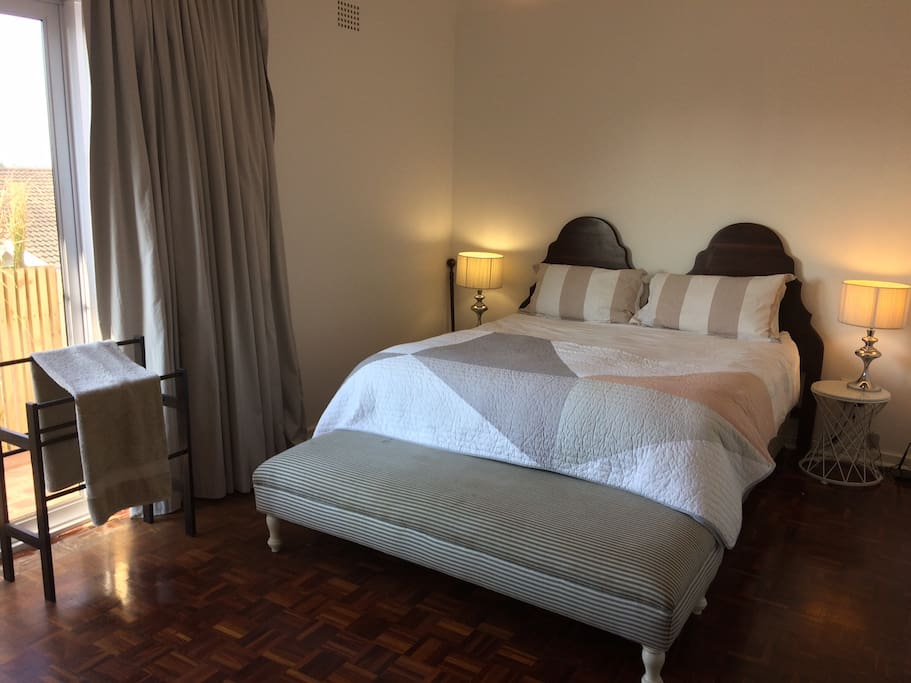 Queen size bed in the main room, including a balcony overlooking the city lights.
