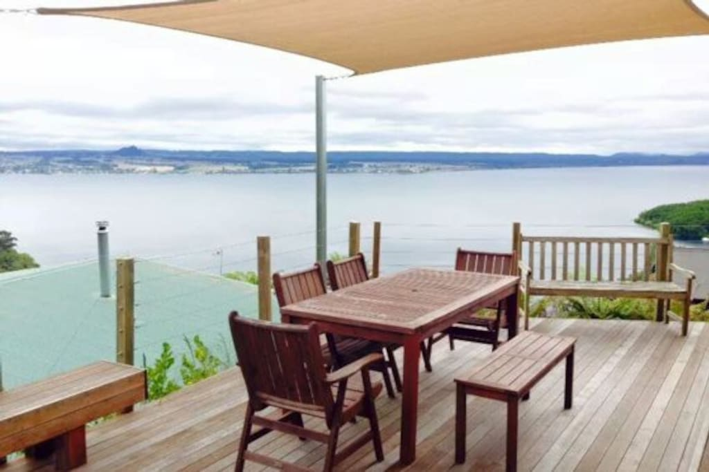 Large sunny deck with shade sail and plenty of seating.