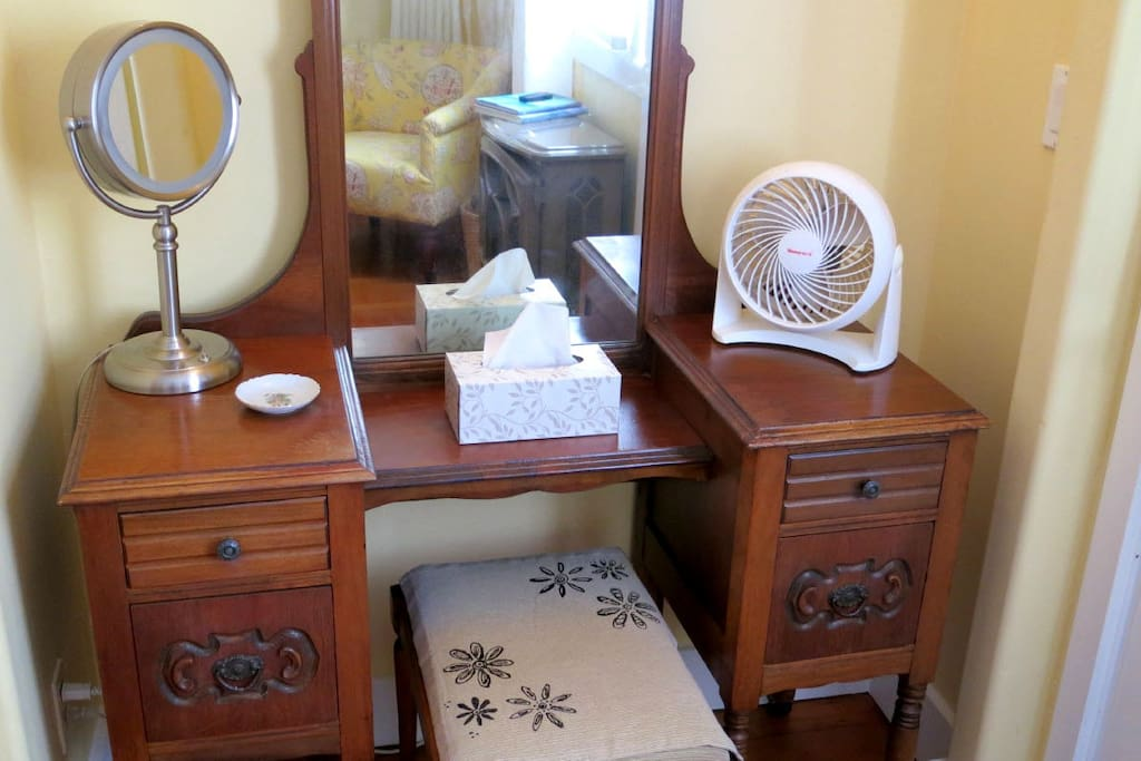 Antique vanity with lighted makeup mirror.