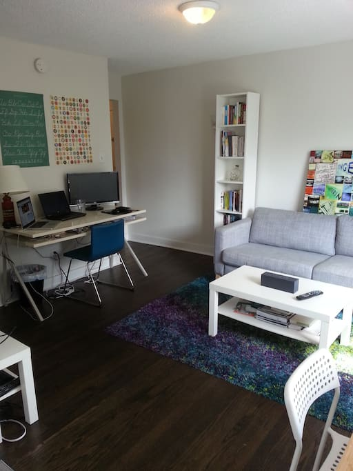 Bright main space with large firm comfy couch (could be used as another bed), large desk, 32-in TV with cable, and small dining table.