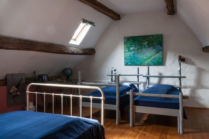 Slaapzolder met twee éénpersoonsbedden en één twijfelaar. Gemeenschappelijke badkamer voorzien van douche, lavabo en wc. Tweede verdieping.