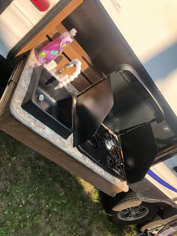 Outdoor kitchen and sink, we love using this feature when we are camping