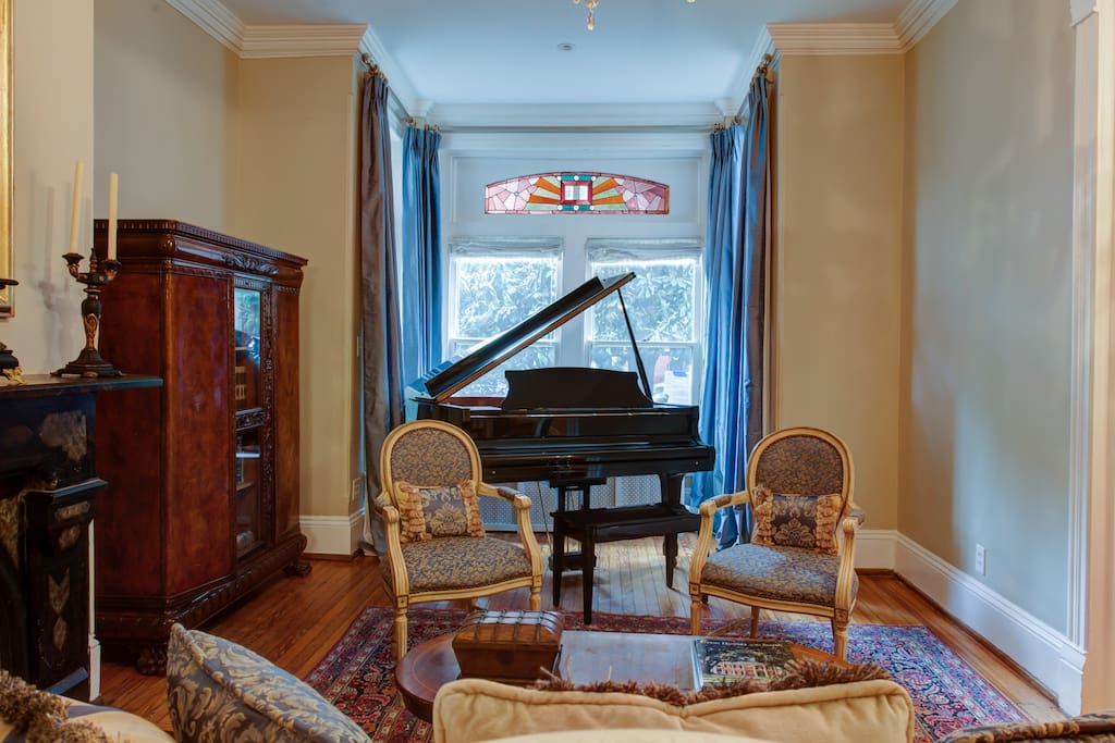 The formal living room includes plenty of seating for guests and a baby grand piano for the musically inclined.