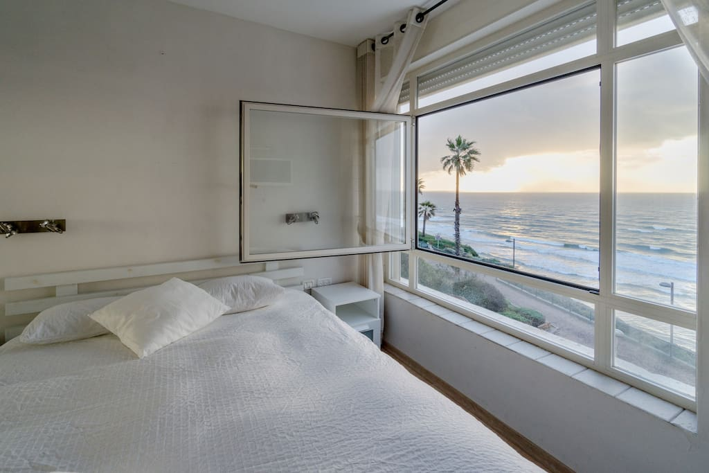 Main bedroom with wall sized window that opens wide to hear the waves below and smell the fresh sea air