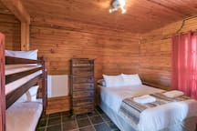 Bedroom with double bed and double bunk.