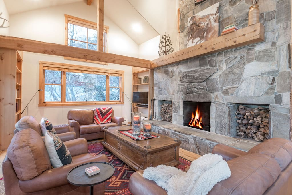 Spacious main floor living room with wood burning fireplace, flat screen TV, and expansive views of the slopes. Seating for 6.