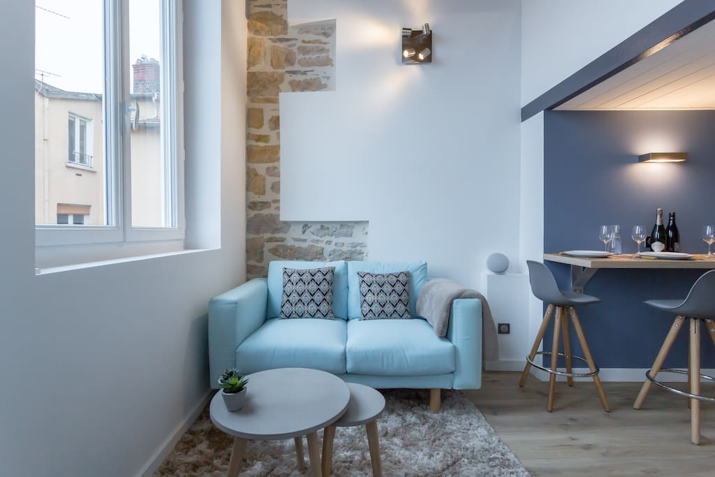 Le canapé douillet du salon devant un mur de pierres!
