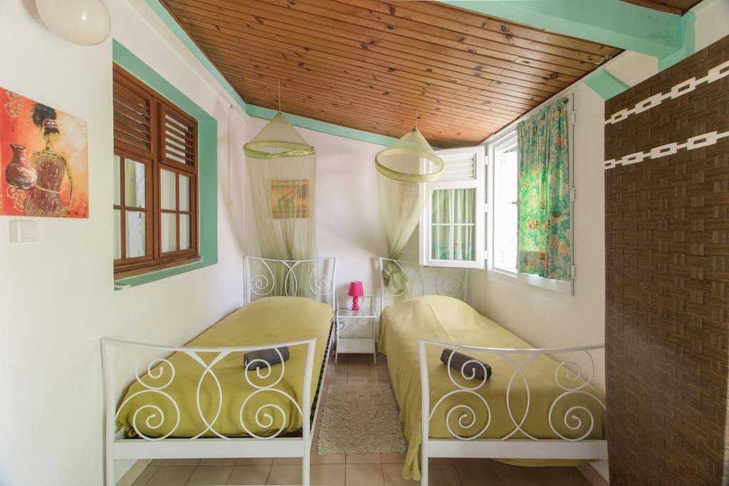 2 lits simples avec moustiquaires