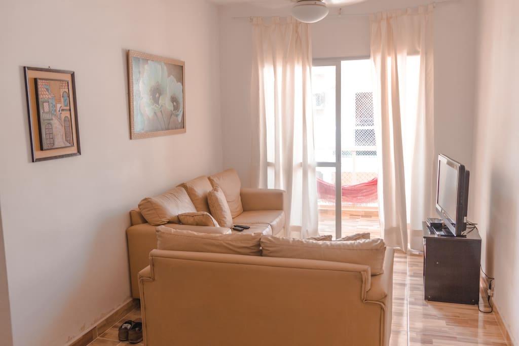 Sala ampla com sofás, tv, mesa de jantar, cortina e sacada com rede para descanso