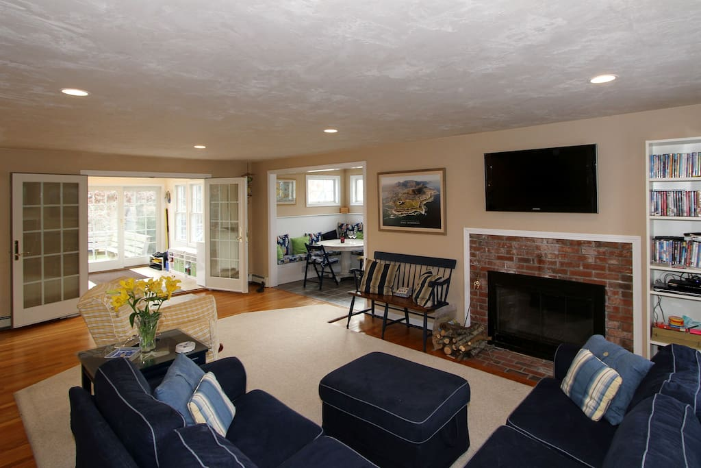 The comfy living room has a large TV over the brick fireplace