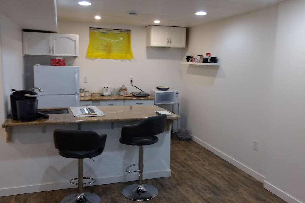 Kitchen with Keurig, induction plate, fridge, microwave, sink, dishes, utensils and implements.