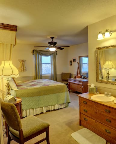 The main part of the room has a king size bed and with easy access to a sink and  vanity.