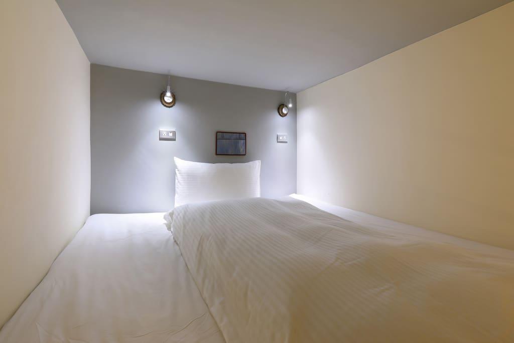 單人房上鋪一大床,有床頭燈、手機收納袋、萬用插座
