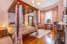 Main bedroom with ensuite. Romantic four poster bed with floral curtains and Sheridan linens. Also furnished with cedar dressing table and wardrobe.