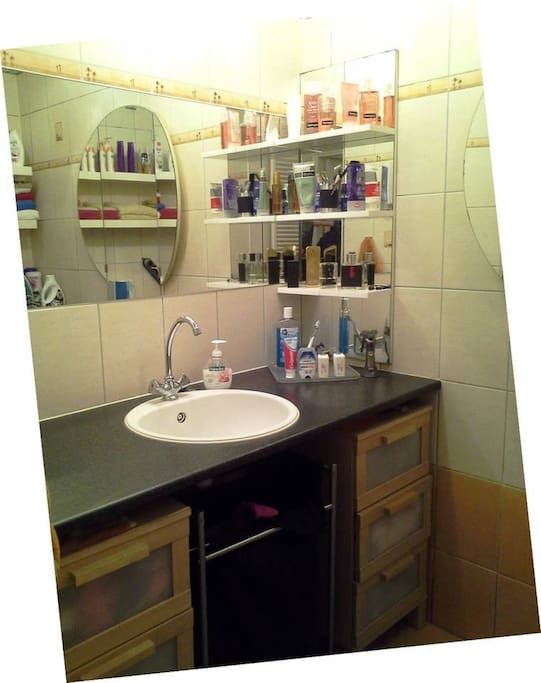 Bathroom with a shower, washer, dryer, ironing board and iron