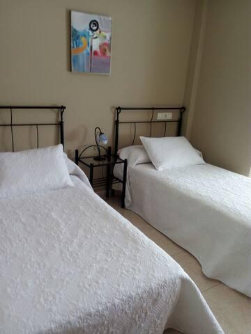 habitación con camas dobles y balcón al exterior