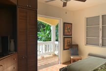 Main bedroom with doors to pool deck. Built in storage & cable TV.