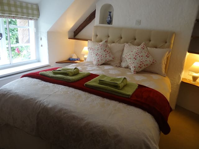 The main bedroom has a comfortable king sized bed with beautiful bedding and plenty of storage