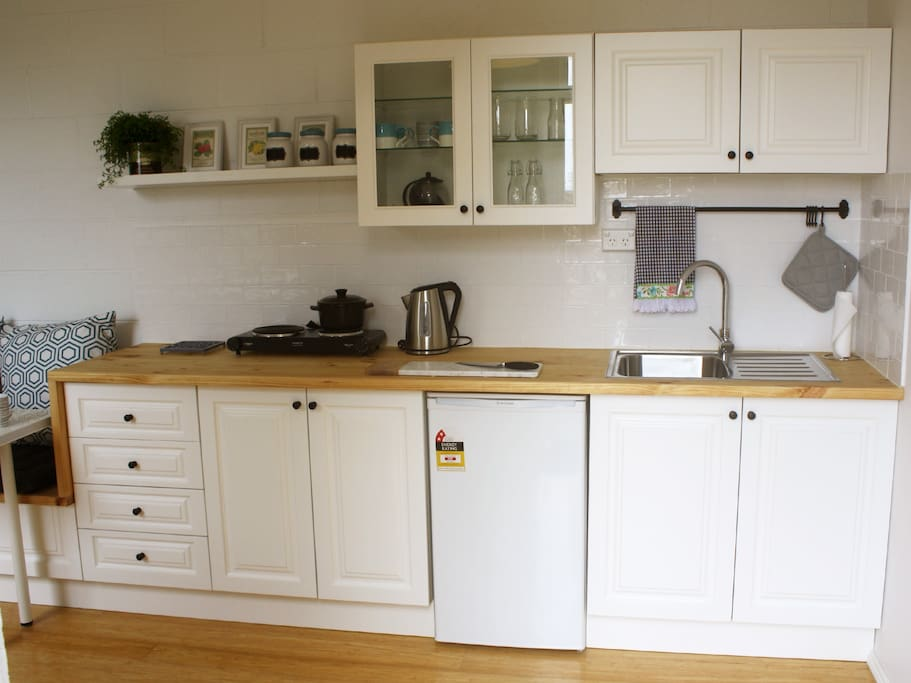 Open plan kitchen, including tea, coffee, a hotplate with pots and pans.