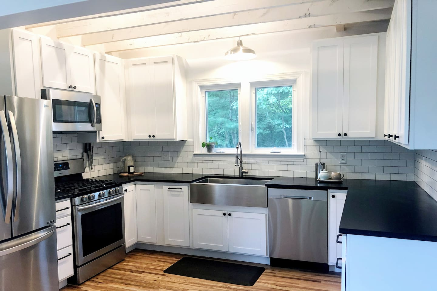 Bright, open kitchen with farm sink and stainless steel appliances