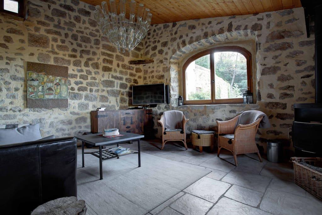 Wohnzimmer mit Couch und Kaminofen, Fernseher, Blick ins Grüne