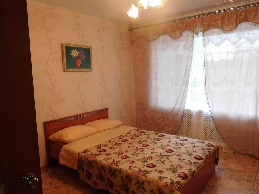 спальня с двухспальной кроватью и комодом.
