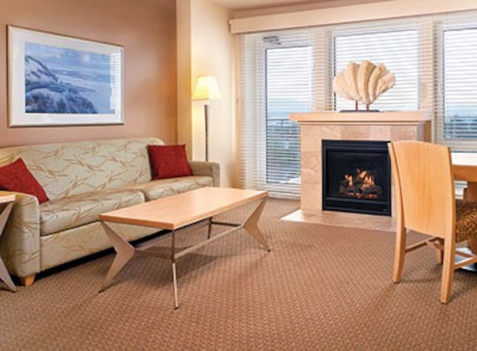 Living room with gas fireplace, queen Murphy bed and balcony with ocean view