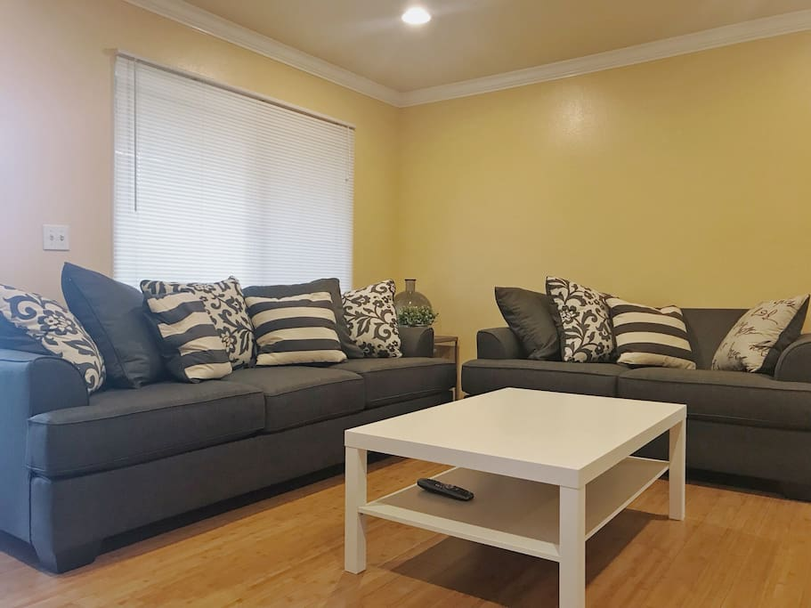 Living room with a huge TV and a pull out sofa bed with foam mattress