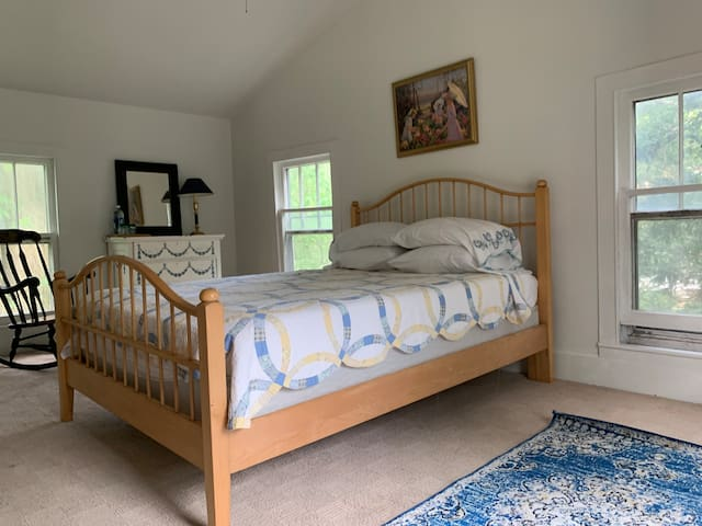 Second bedroom with a queen size bed and hanging space for clothing.