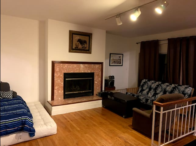 Spacious shared living room with projector screen and fire place