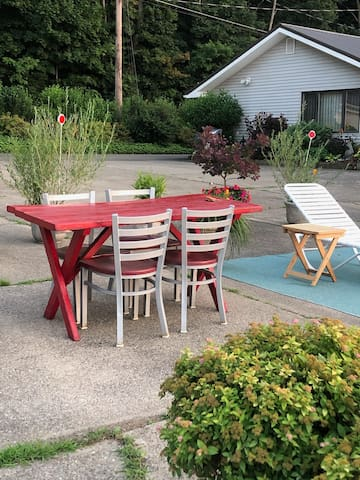 Private designated guest patio area with lounge chairs, benches, side tables, and a picnic table.