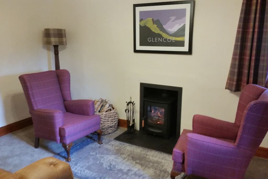 Sitting ting room with log burner and double sofa bed.