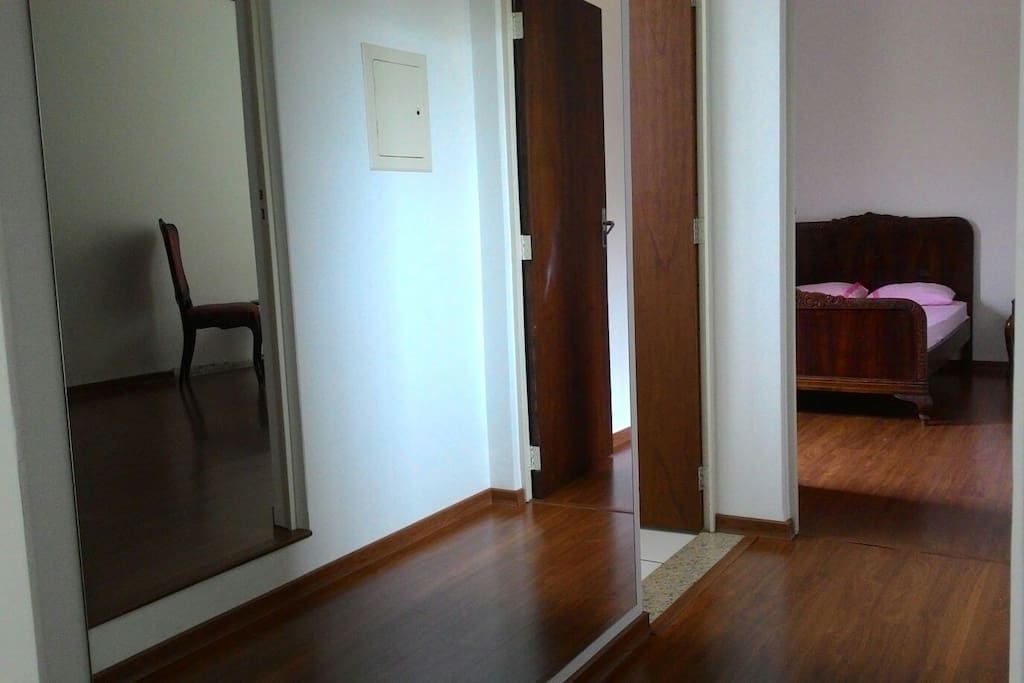 corredor com espelho em toda a parede,mostrando acesso ao quarto maior