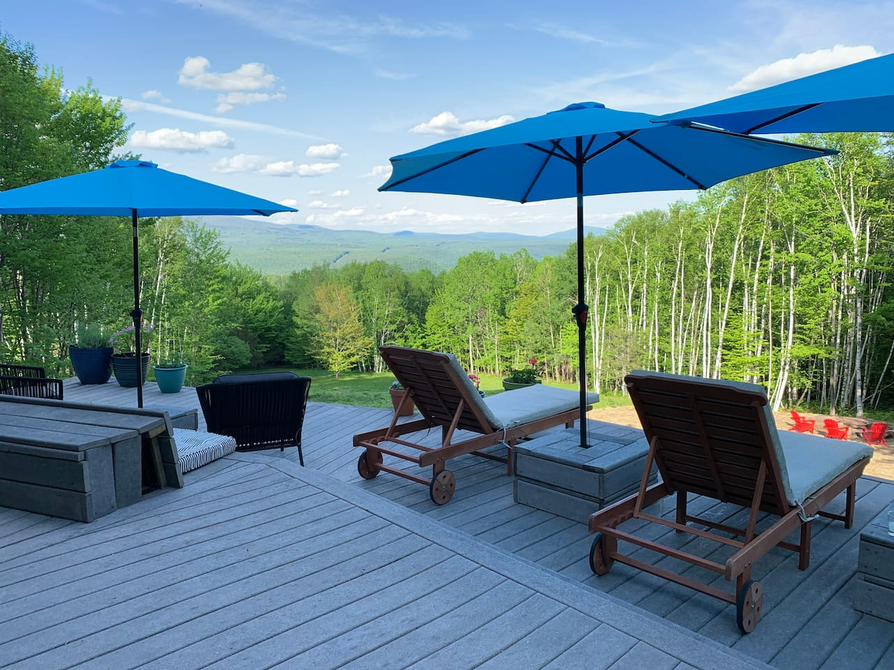 New patio setup for summer 2019 includes ample seating (including a 13 ft long bench), chaise lounges, dining area, and propane grill facing the magnificent view