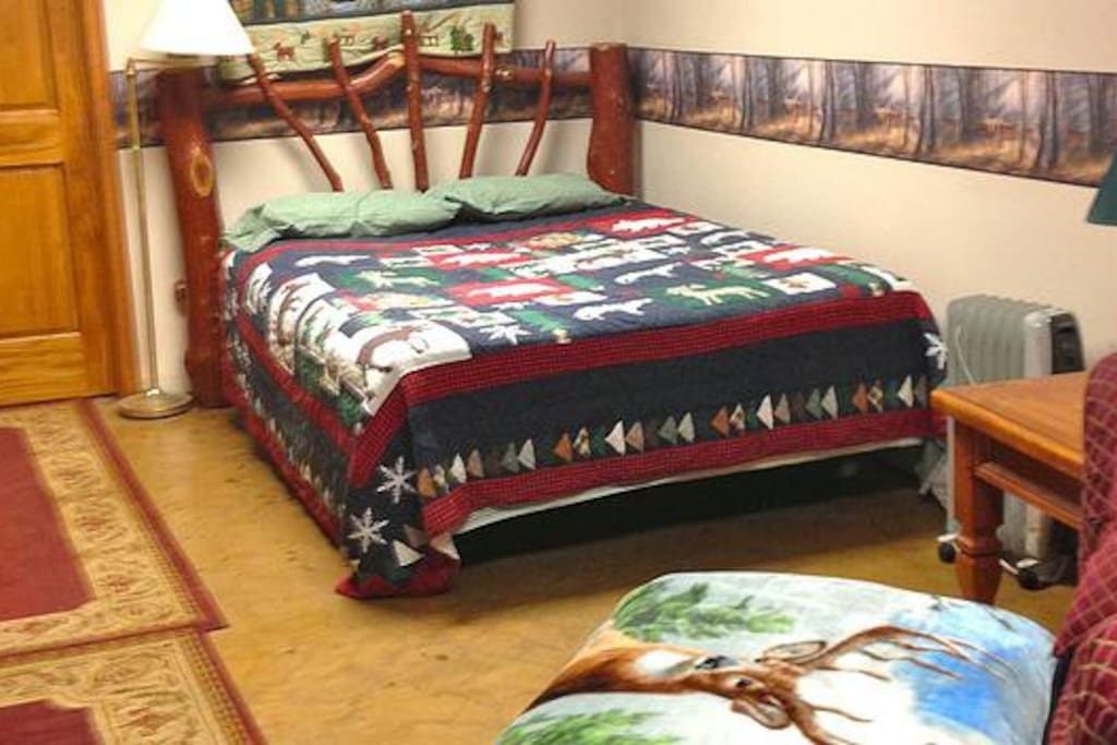 Spacious bedroom with queen bed, couch, dresser, closet, cable TV, WiFi internet, and a desk.