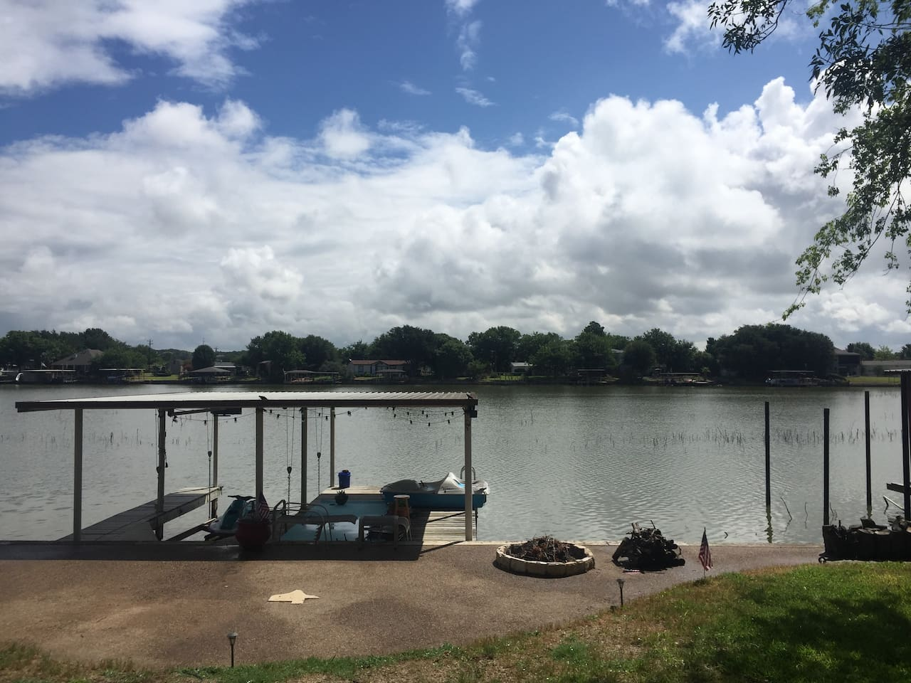 Standing on porch looking at  Covered Boat Dock.   Large back yard to enjoy. Yes Lake is really that close  Bring your water toys to enjoy just off our dock
