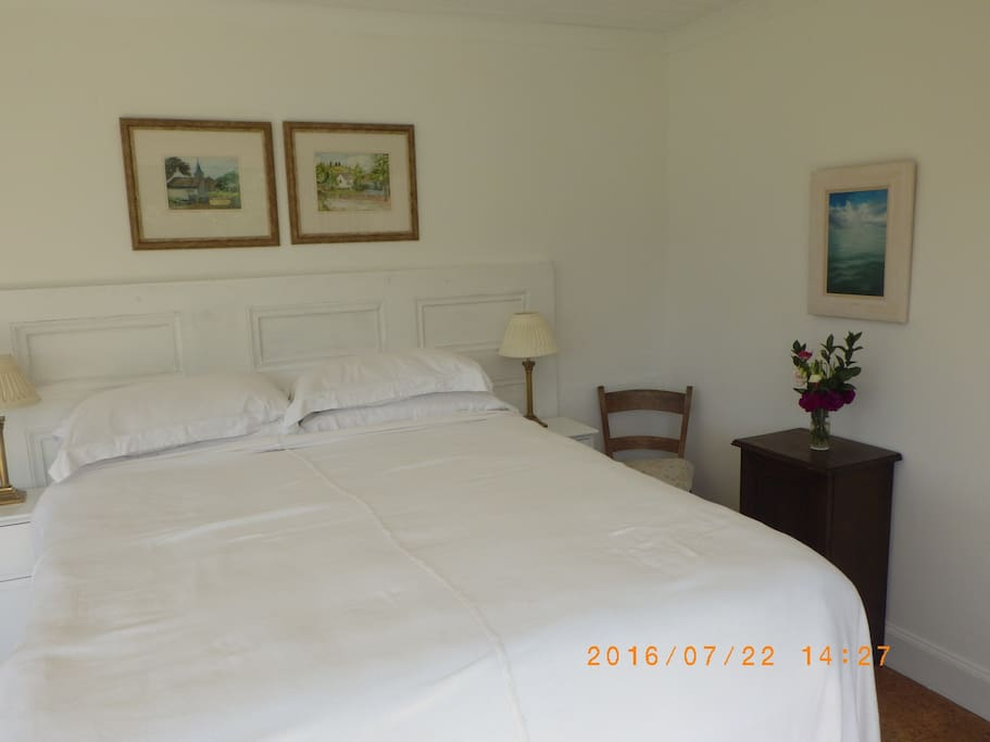 A large double bed with family paintings