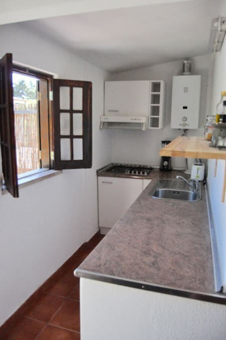 Bright, self-catering kitchen with stove, refrigerator and storage