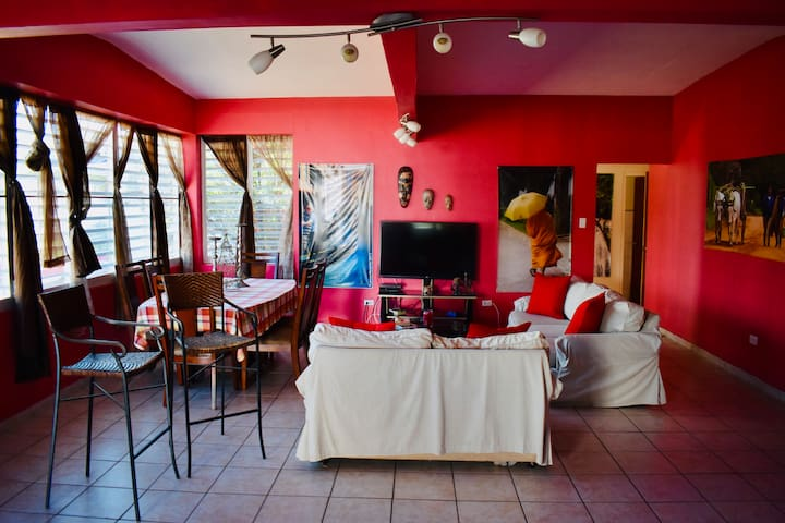 Living room with AC, TV, Cable TV, DVD player, WIFI,  one pair of sofas, stools and dinning table with 6 chairs.