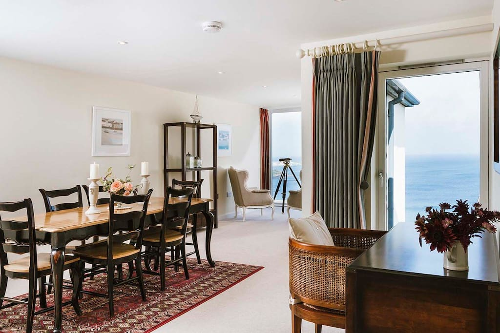 Large dining table with space for 6 (perfect for family meals) leading to Captain's Chair with telescope and sea views