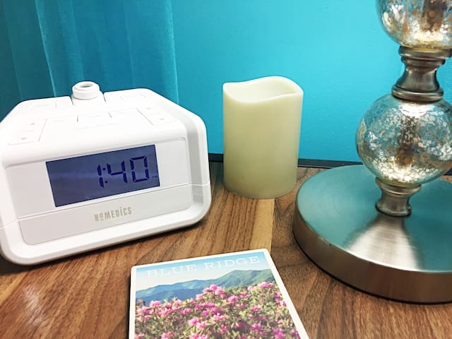 We provide a special clock-radio that has optional white noise and other nature sounds. It also has an option to project the time onto the ceiling so you can see it from bed.